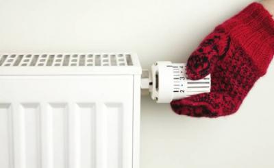 Main dans un gant en laine rouge qui règle la température d'un radiateur
