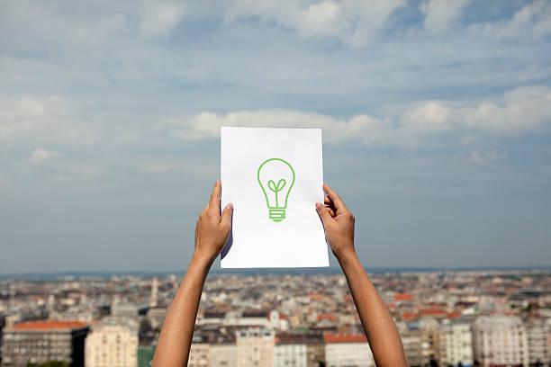 Femme qui tend en l'air une feuille avec le dessin d'une ampoule verte, avec en arrière-plan une ville
