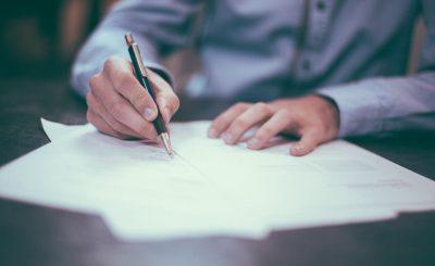 Homme en train d'écrire au stylo sur une tas de feuilles blanches de réglementation et de normes