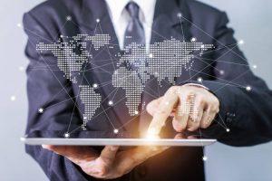 Homme en costume tenant une tablette projetant une carte du monde avec ses connexions