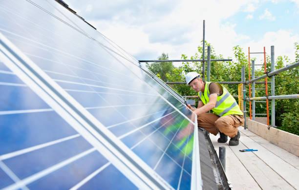 Homme en tenue de travail qui installe des panneaux solaires sur un toit