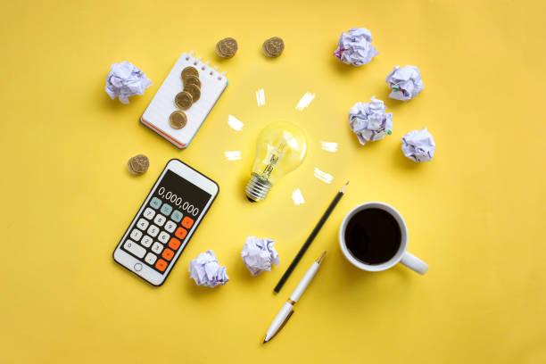 Ampoule vue de haut sur fond jaune avec téléphone portable, tasse de café, boules de papier et stylos autour