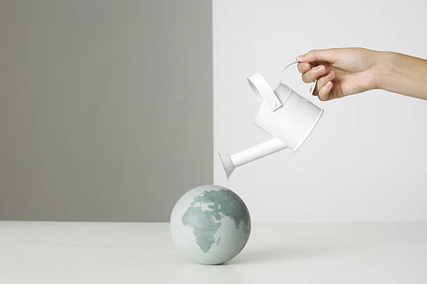 Globe terrestre arrosé par un petit arrosoir blanc