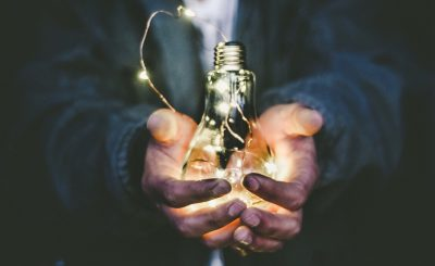 Homme tenant dans ses mains une ampoule électrique allumée