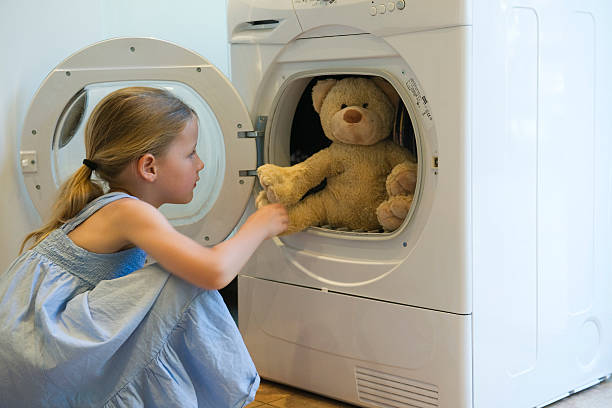 Petite fille en train de mettre son ours en peluche à la machine à laver