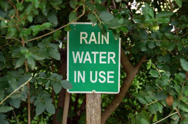 """Panneau vert avec l'inscription """"Rain water in use"""", soit """"utilisation de l'eau de pluie"""""""