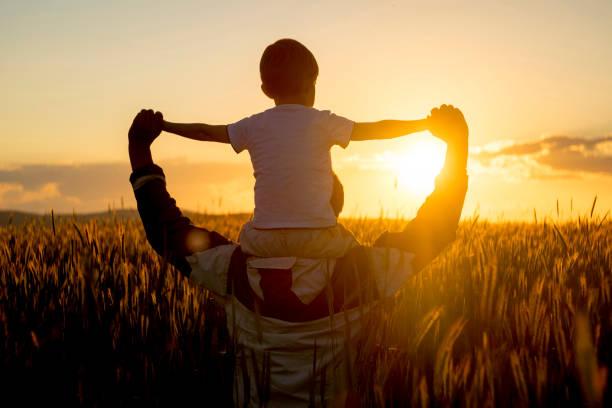 Père portant son enfant sur les épaules dans un champ face au soleil