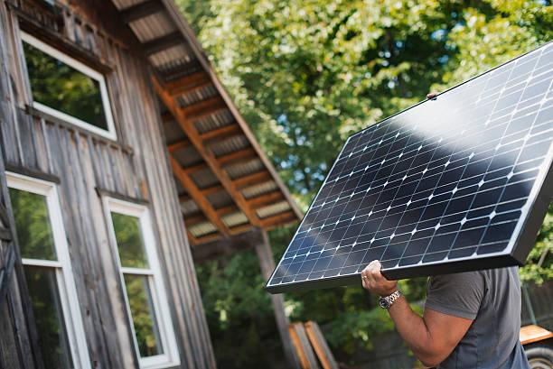 Homme qui porte un panneau solaire avec une maison en bois en arrière-plan
