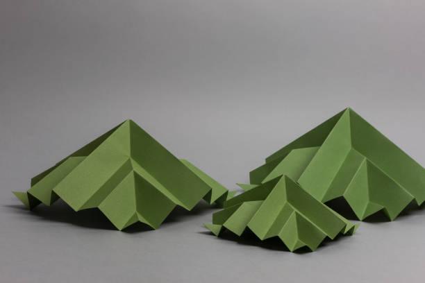 Origamis en papier vert : trois pyramides pour représenter des maisons