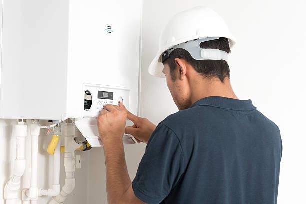 Plombier qui répare une chaudière en panne