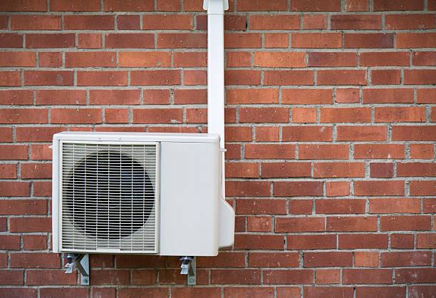 Pompe à chaleur installée sur un mur extérieur en brique