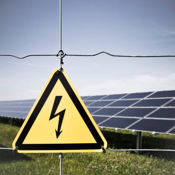 """Panneau """"danger"""" devant un champ de panneaux solaires photovoltaïques"""
